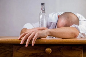 Drunk guy passed out on desk with empty bottle