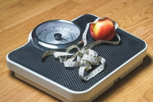 Weight scale with apple and measuring tape on it.