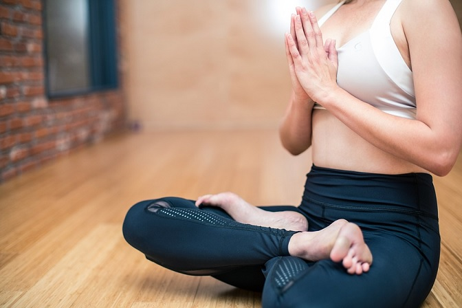 Woman meditating alone and wearing black yoga pants