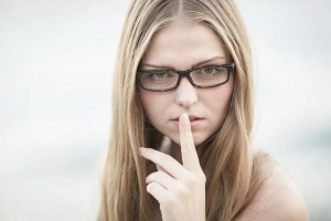 Woman with finger in front of mouth saying to be quiet