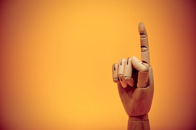 Wooden model hand with finger pointed upward
