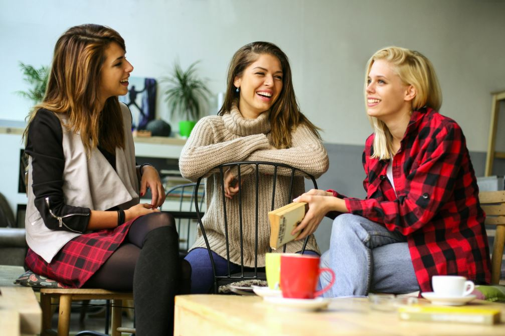 Three women talking inside room, drinking coffee.