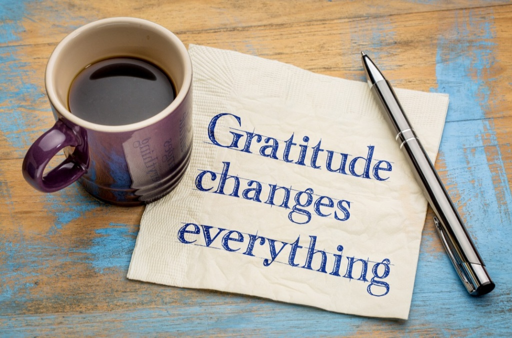Coffee cup on table, with pen with paper with words written on it - gratitude changes everything