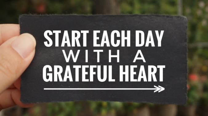 A small sign held in someone's hand with the words Start each day with a grateful heart