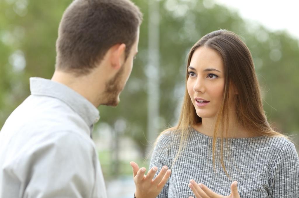 Woman talking to man outside