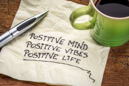 Positive mind, positive vibes, positive life me. Words written on napkin by coffee cup and pen.