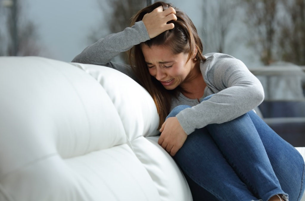 Woman on white couch, crying, wearing blue jeans and grey shirt.