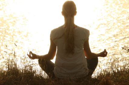 Woman meditating in field by water, sun shinning.